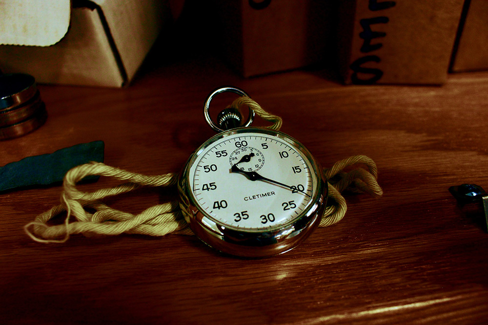 white-pocket-watch-with-gold-colored-frame-on-brown-wooden-1010513
